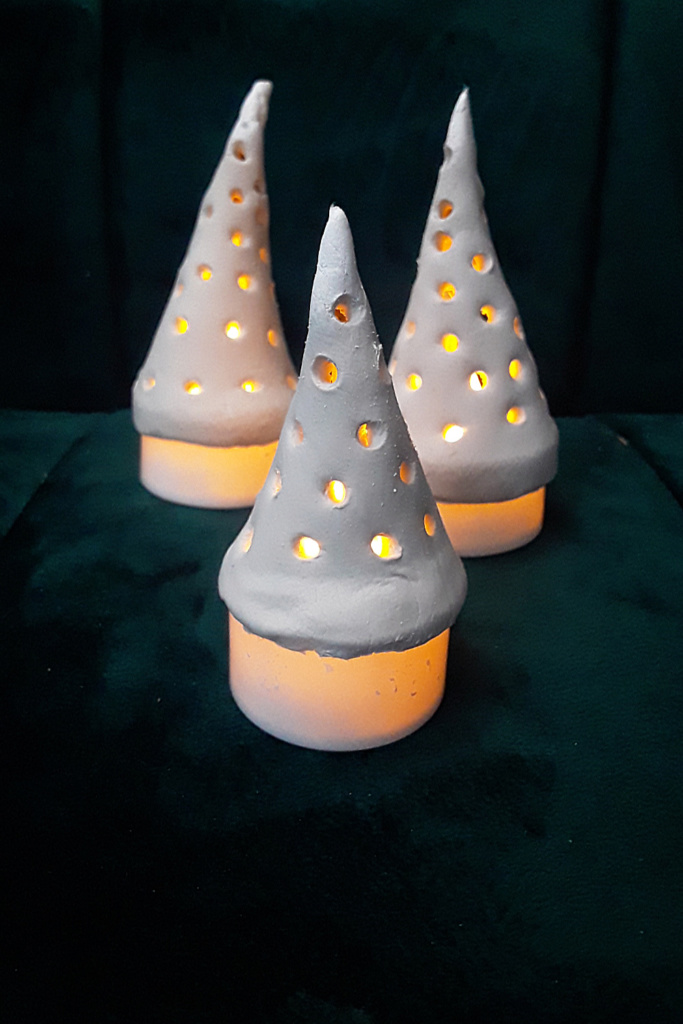 DIY Christmas Craft - Cute little air dry Christmas trees perfectly lit by faux flame tea lights This is so easy and inexpensive and perfect for you Christmas village or mantel or anywhere you need a tiny touch of Christmas.
